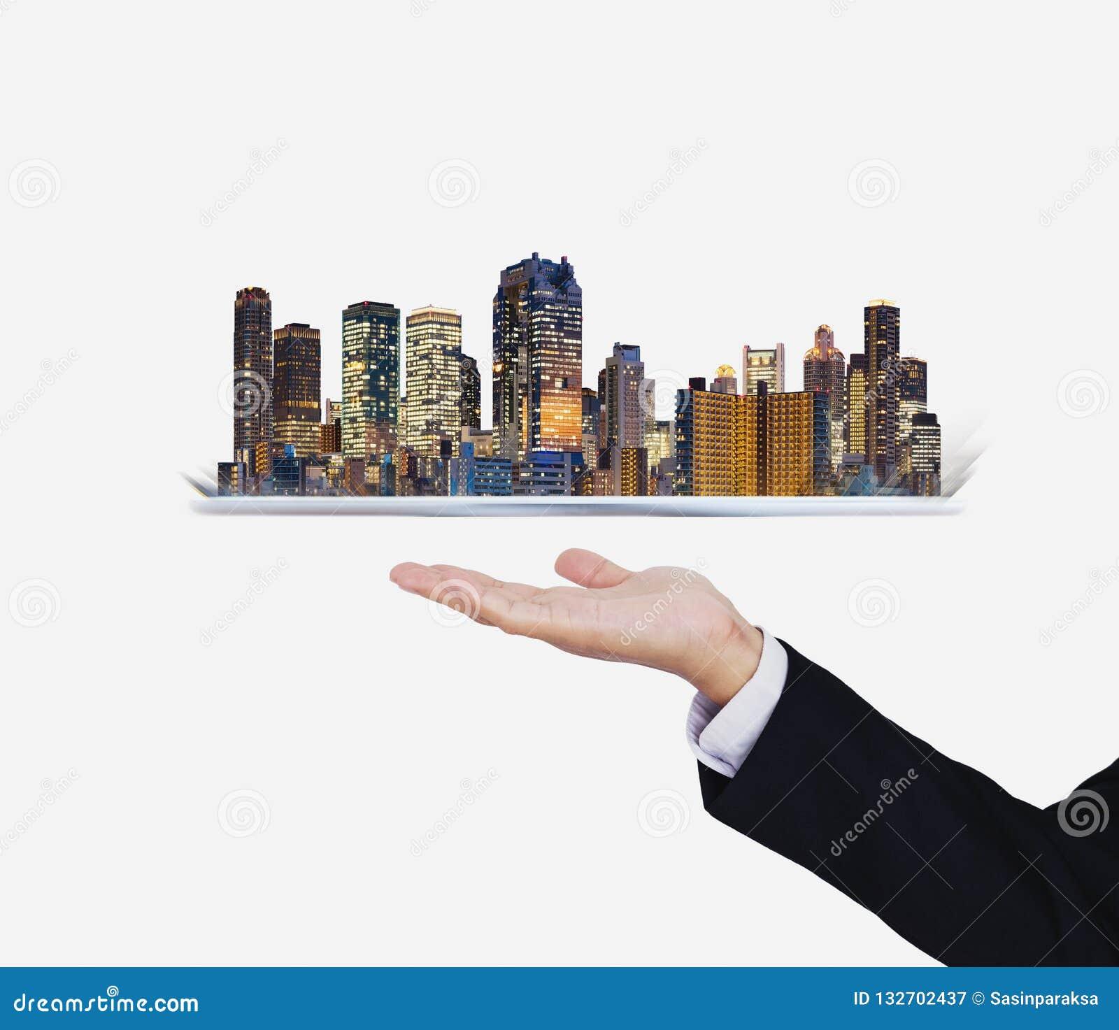 拿着有现代大厦全息图的商人手数字片剂 聪明的城市、建筑技术和不动产事务