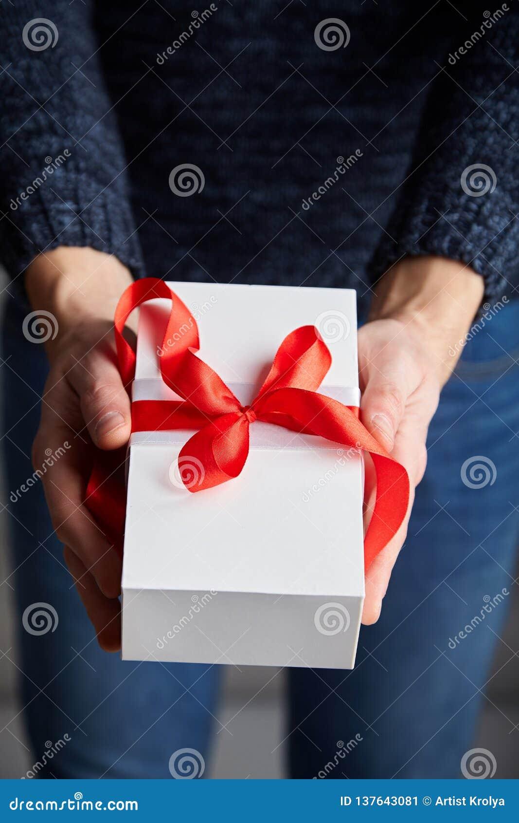 拿着有红色丝带的一个人白色礼物盒在他的手上