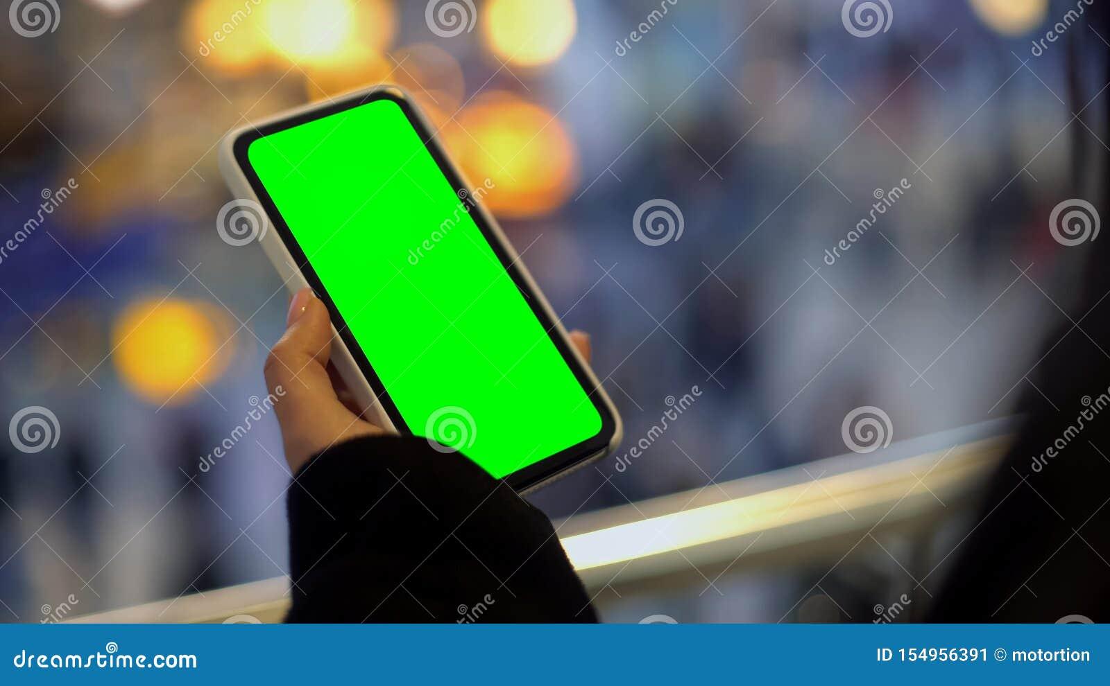拿着有绿色屏幕的妇女手机,站立在购物中心,广告