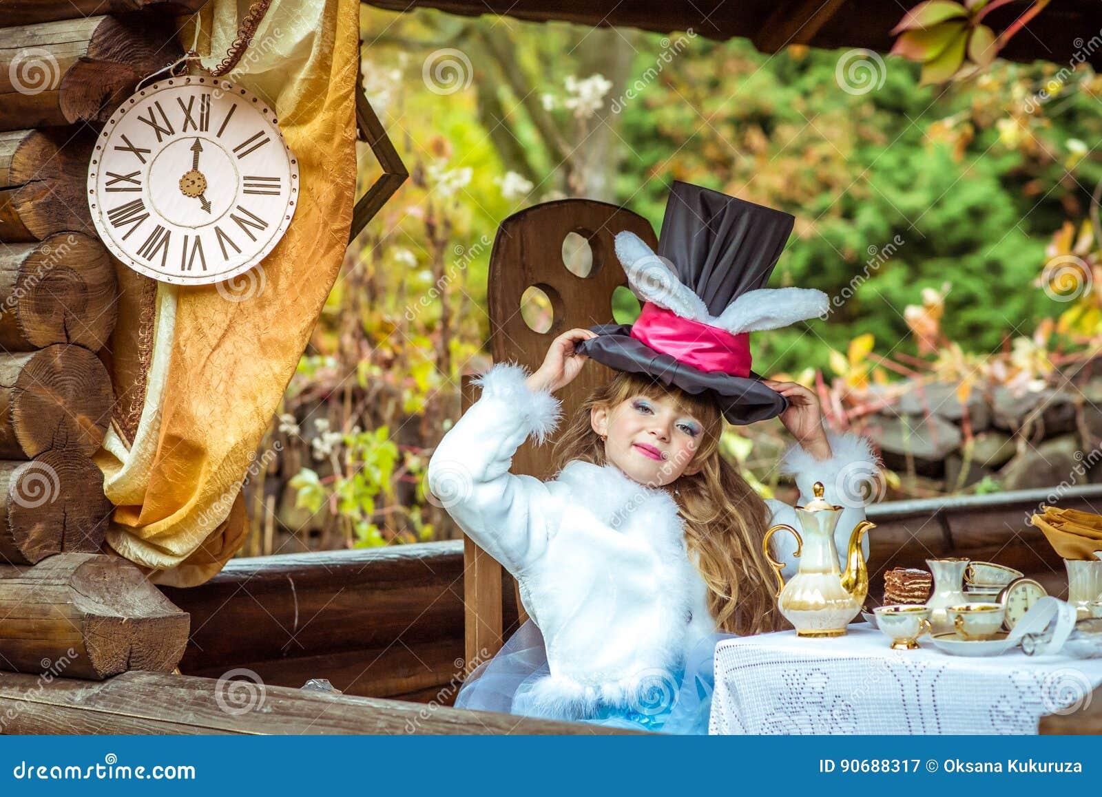 拿着有耳朵的一个小美丽的女孩圆筒帽子喜欢兔子顶上在桌上