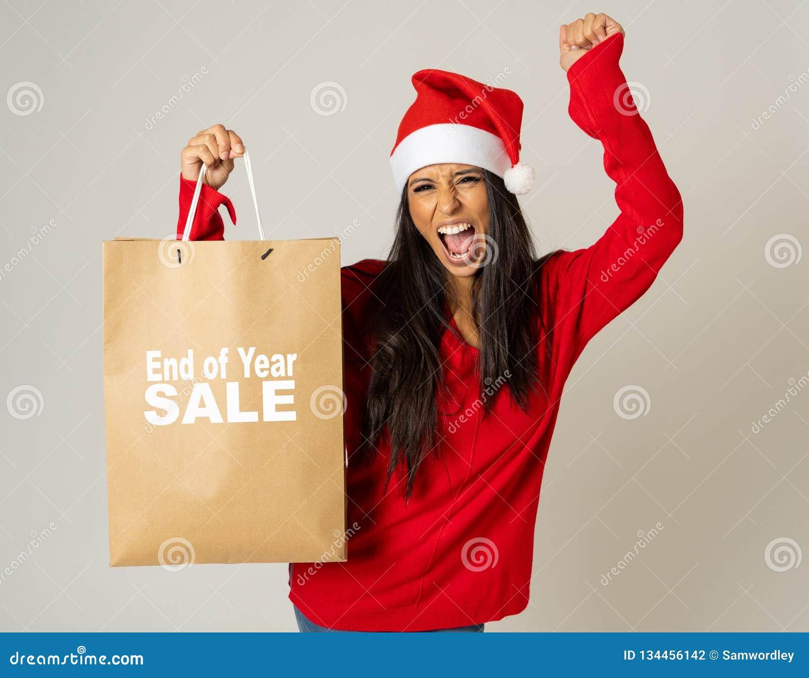 拿着有销售的圣诞老人帽子的妇女圣诞节购物带来写对此看起来激发和愉快