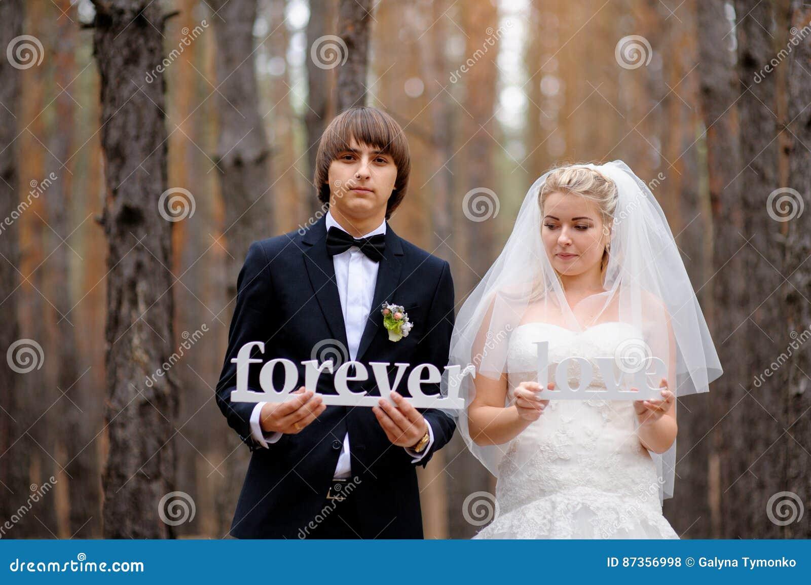 拿着木信件的新娘和新郎永远爱