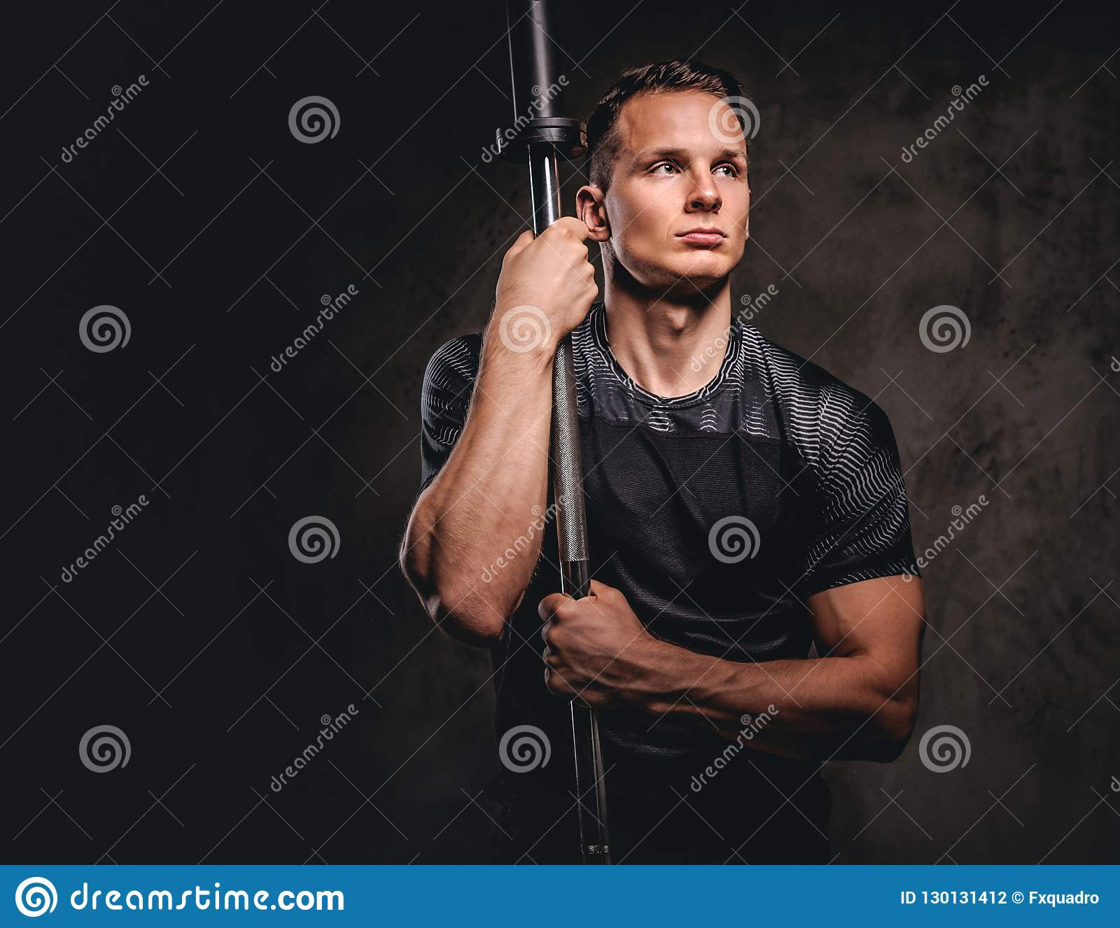 拿着杠铃和看在黑暗的背景的一个英俊的年轻爱好健美者的画象