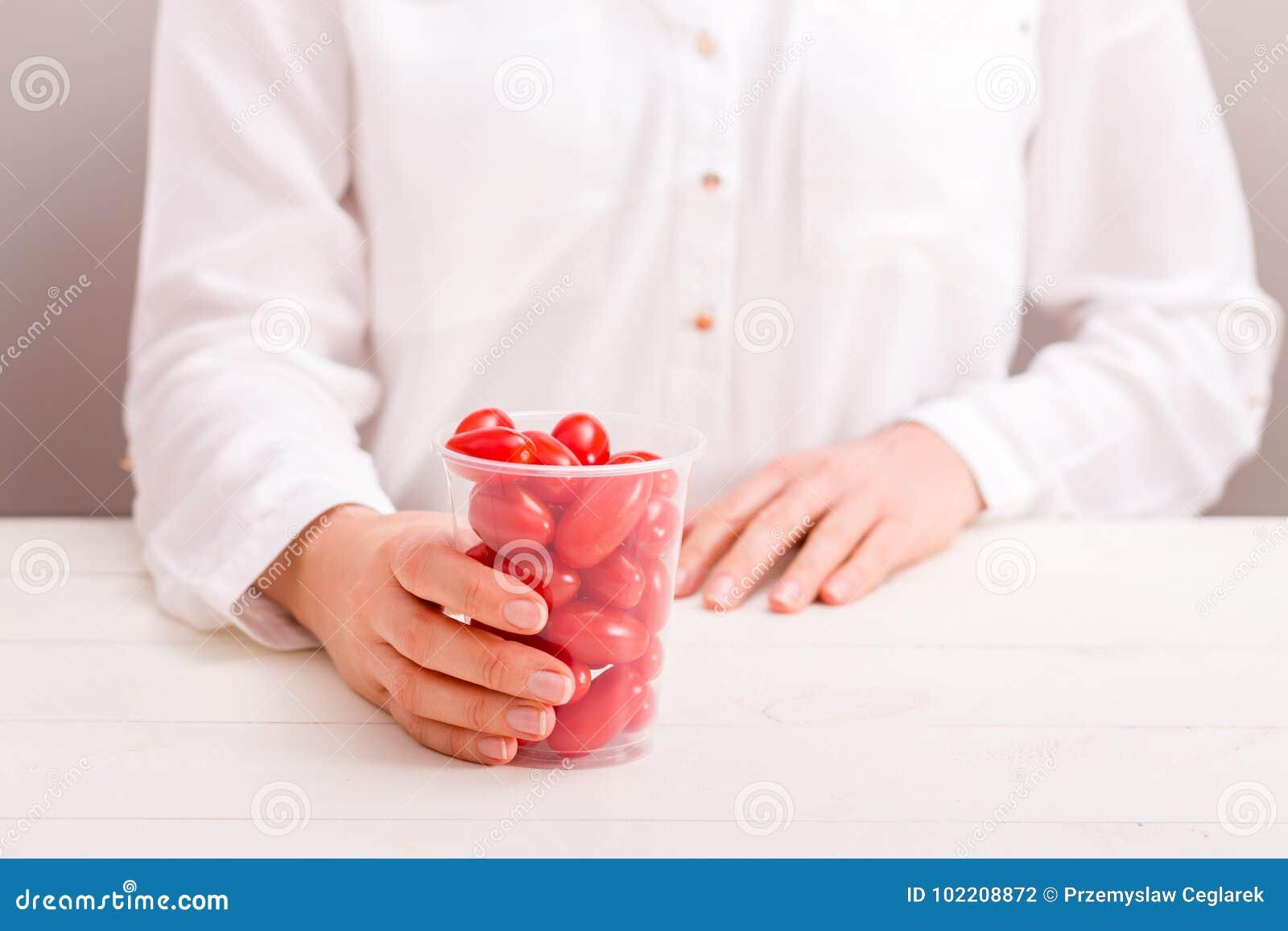 拿着杯子用新鲜的小蕃茄的女实业家