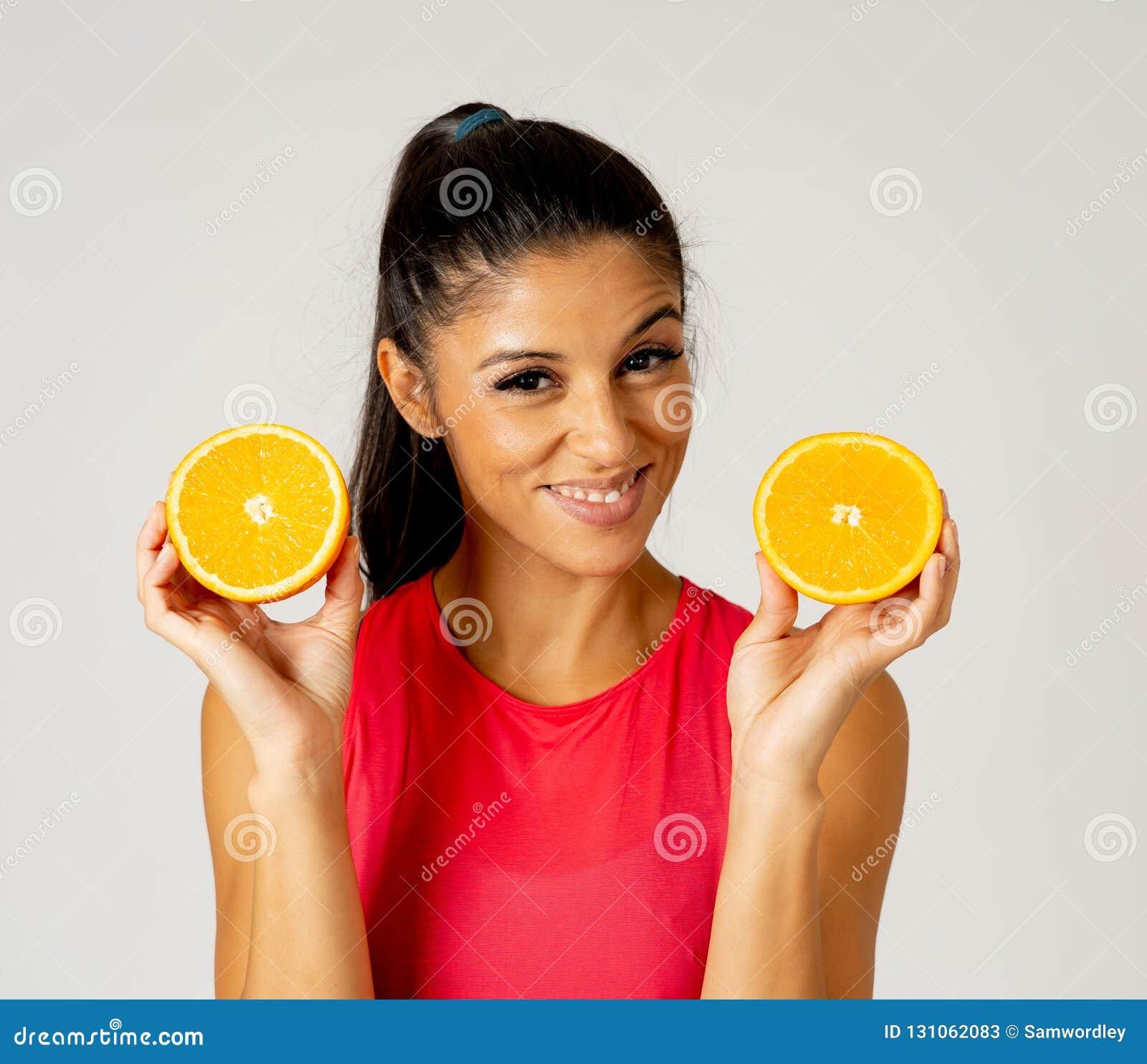 拿着杯新鲜的橙汁和橙色果子的愉快的可爱的运动的妇女