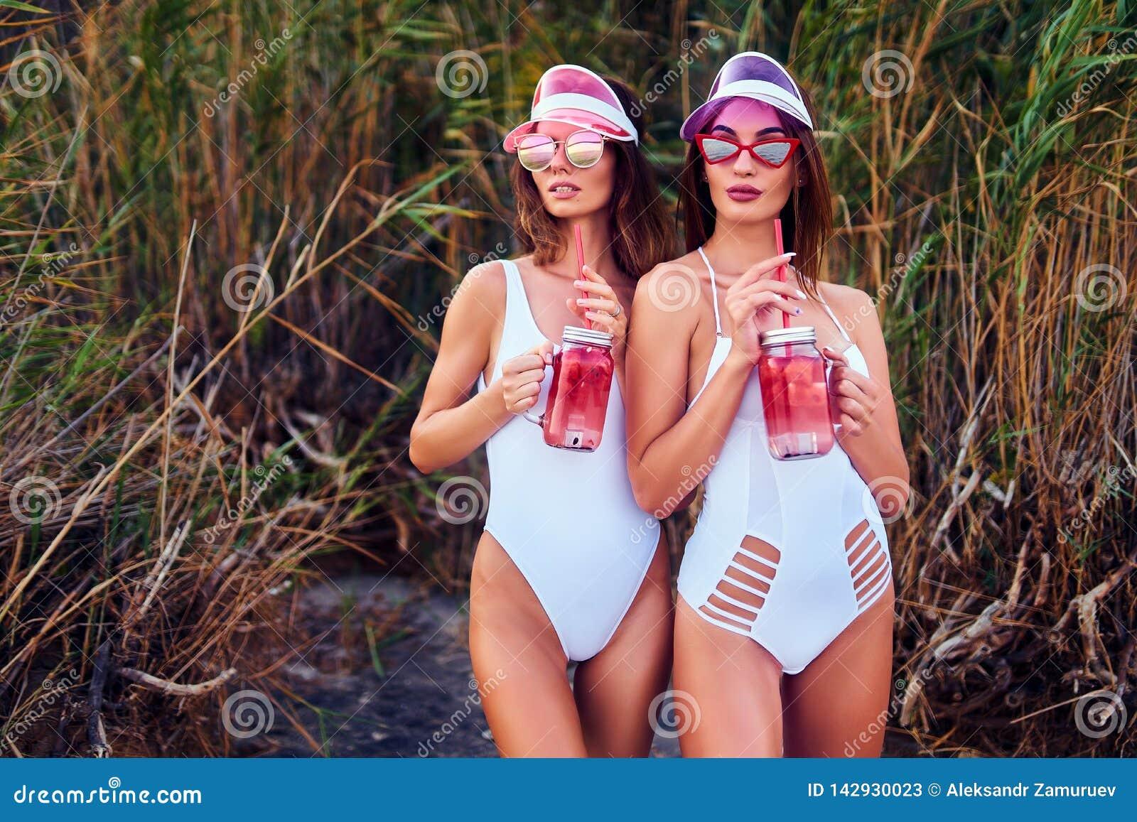 拿着柠檬水的泳装的时髦女孩