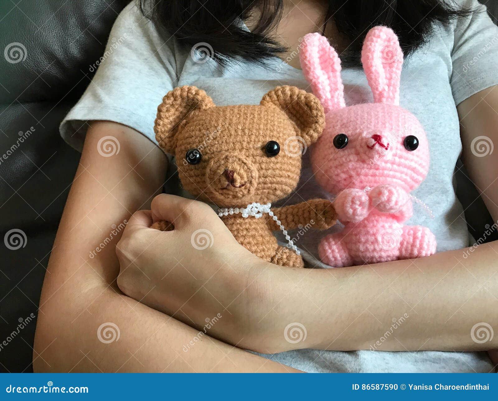 拿着棕色玩具熊ans桃红色兔宝宝钩针编织玩偶的女孩