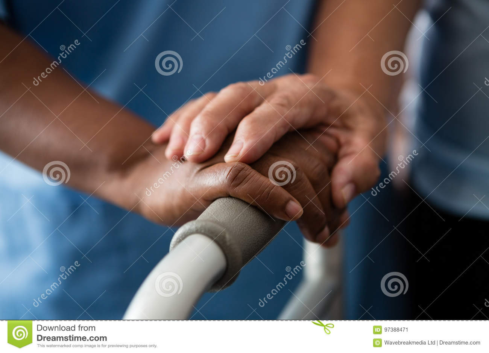 拿着步行者的护士和资深妇女的手在老人院
