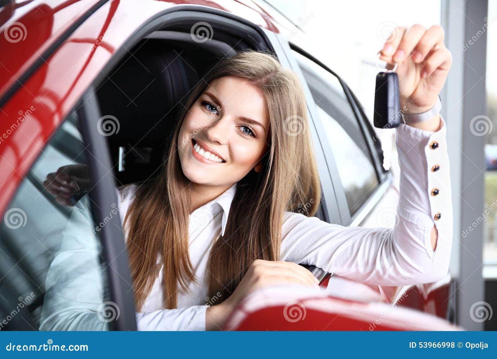 拿着汽车的妇女司机锁上在新的汽车的选址