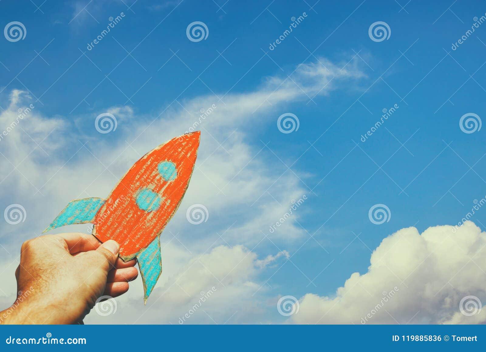 拿着火箭的男性手的图象反对天空 想象力和成功概念