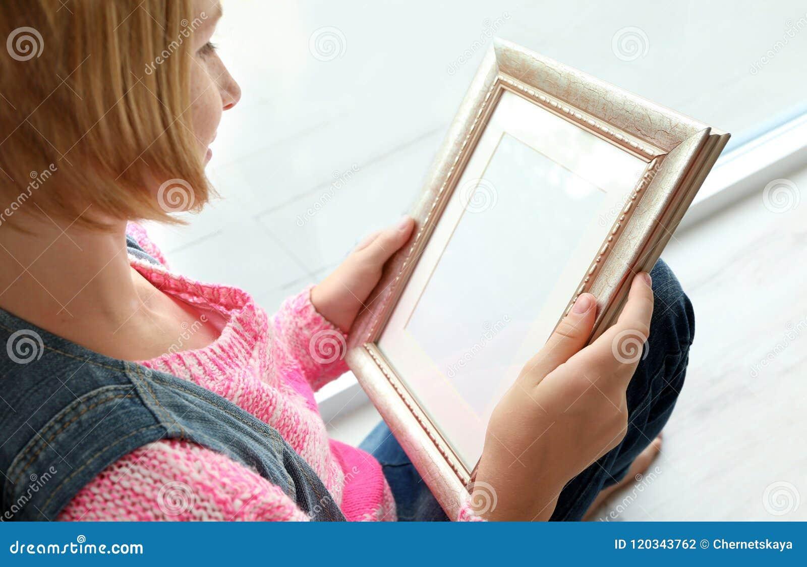 拿着照片框架和坐在窗口附近的少年女孩