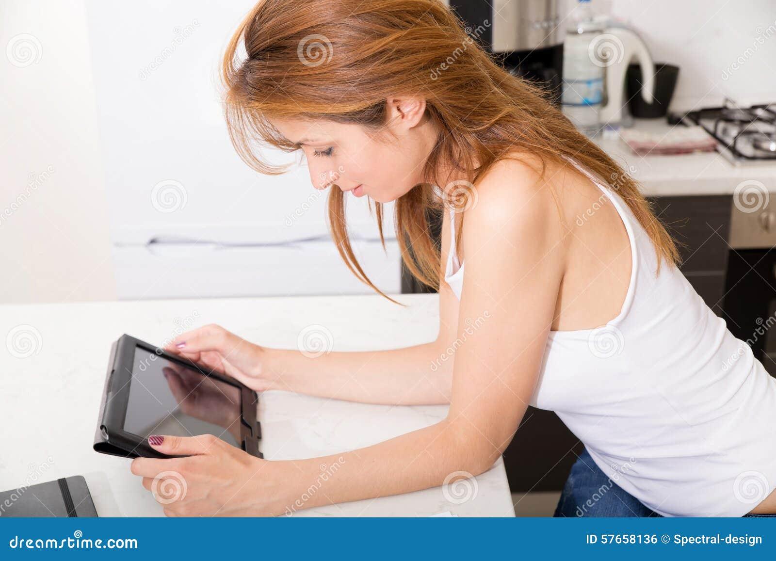 拿着片剂个人计算机的红头发人女孩在厨房里
