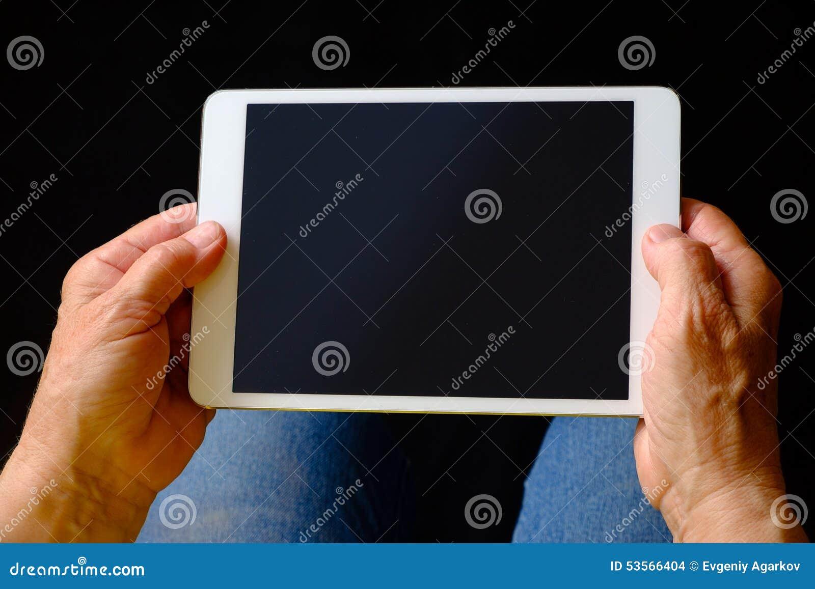 拿着片剂个人计算机的资深妇女的手