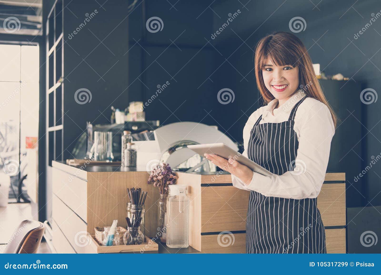 拿着片剂的小企业主在咖啡店的柜台 f