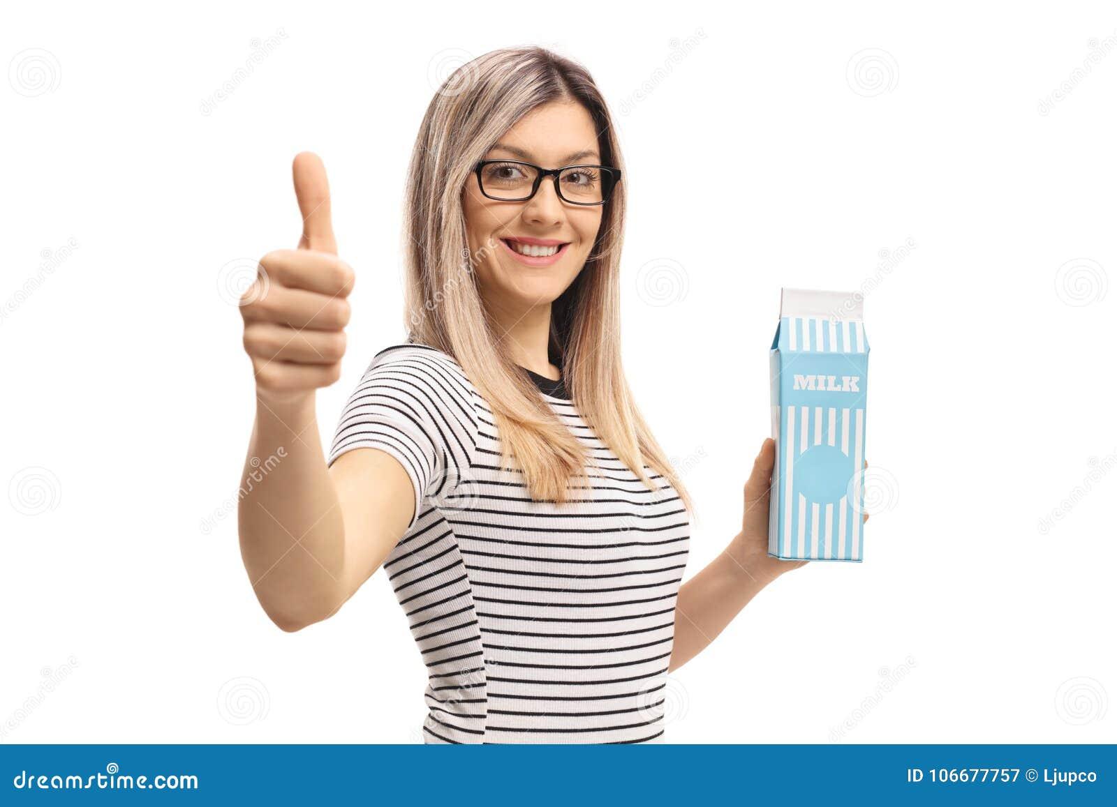 拿着牛奶纸盒和做赞许标志的少妇