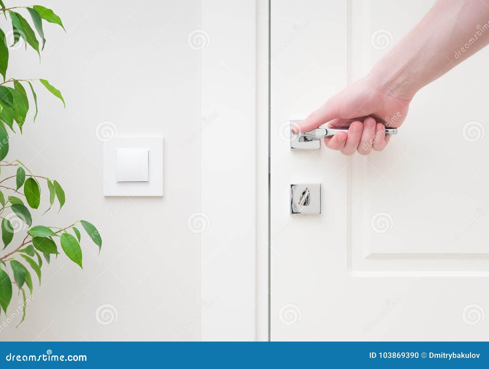 拿着现代门把手的男性手 apartmen的内部的特写镜头元素