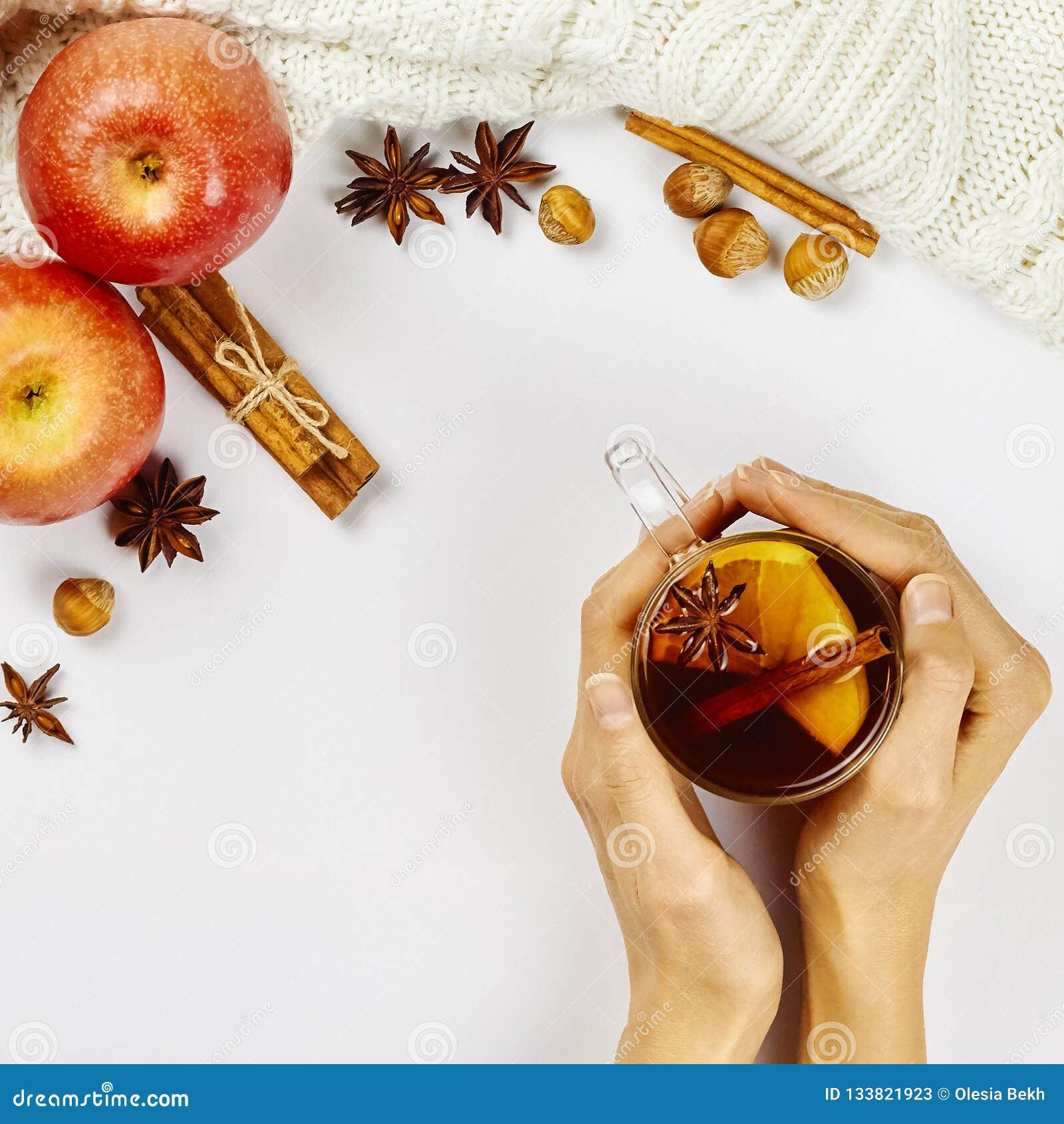 拿着玻璃杯子热的辣发球区域用苹果和橙色切片,桂香和茴香的女性手在白色背景