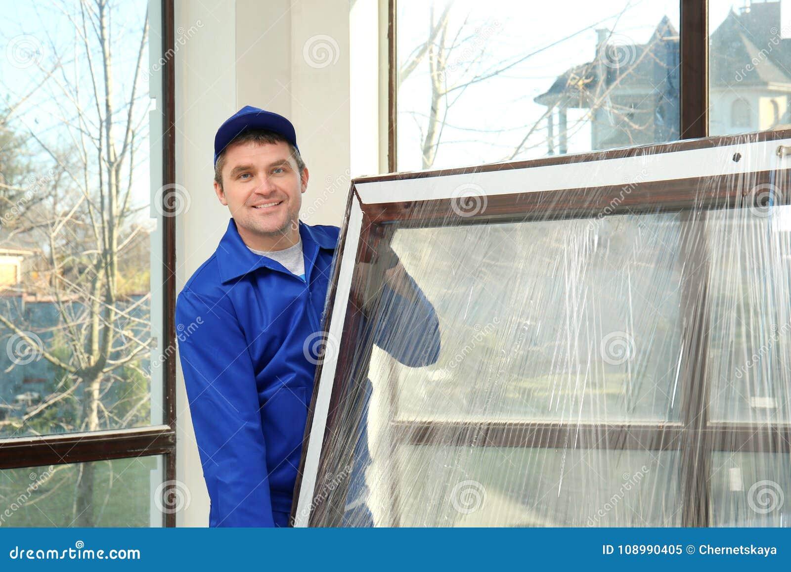 拿着玻璃窗的建筑工人
