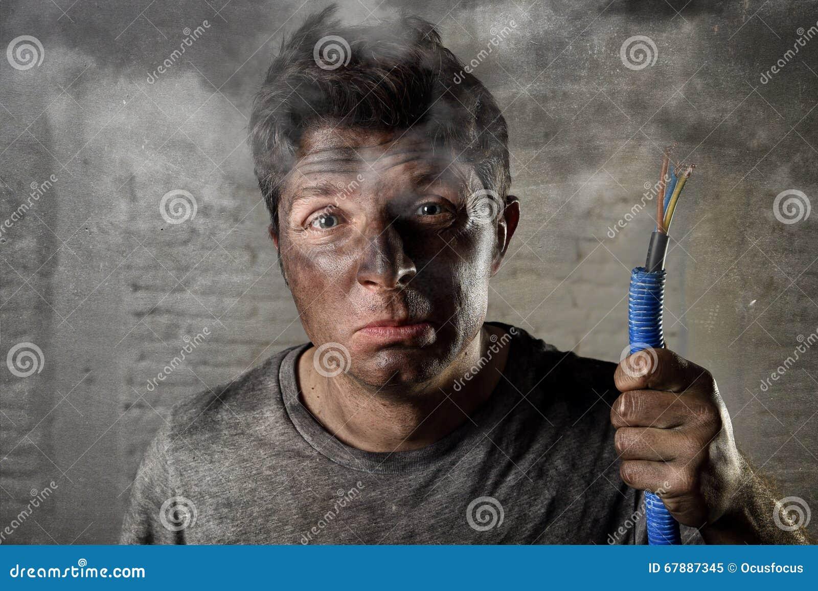拿着电缆的年轻人抽烟在与肮脏的被烧的面孔的电子事故以后在滑稽的哀伤的表示