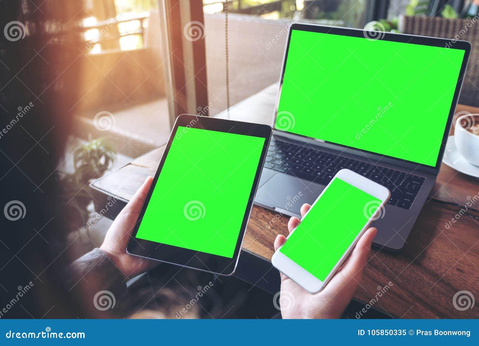 拿着白色手机、黑片剂和膝上型计算机有空白的绿色屏幕的女实业家的大模型图象在葡萄酒木选项
