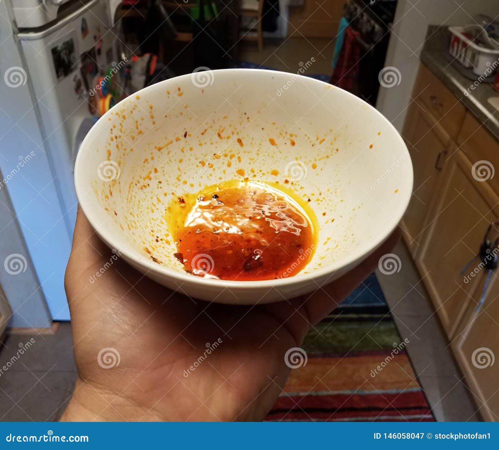 拿着白色碗红色油的手在厨房里