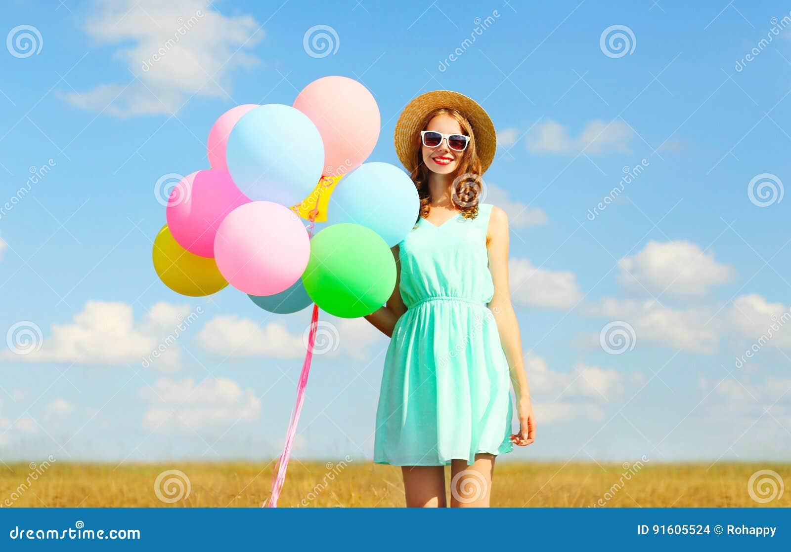 拿着空气五颜六色的气球享受在草甸蓝天的愉快的微笑的少妇一个夏日