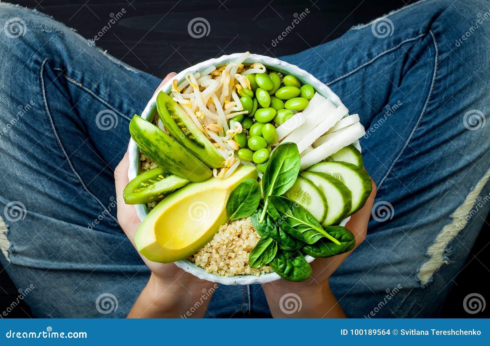 拿着素食主义者,戒毒所绿色菩萨碗的牛仔裤的女孩用奎奴亚藜,鲕梨,黄瓜,菠菜,蕃茄,绿豆新芽, edamame
