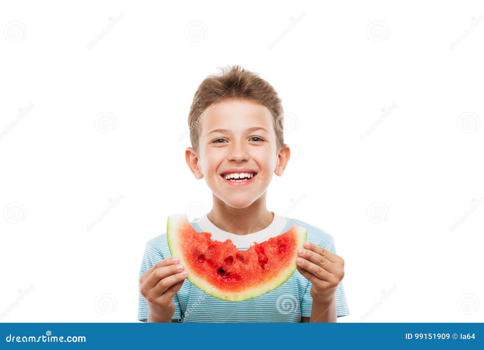 拿着红色西瓜果子切片的英俊的微笑的儿童男孩