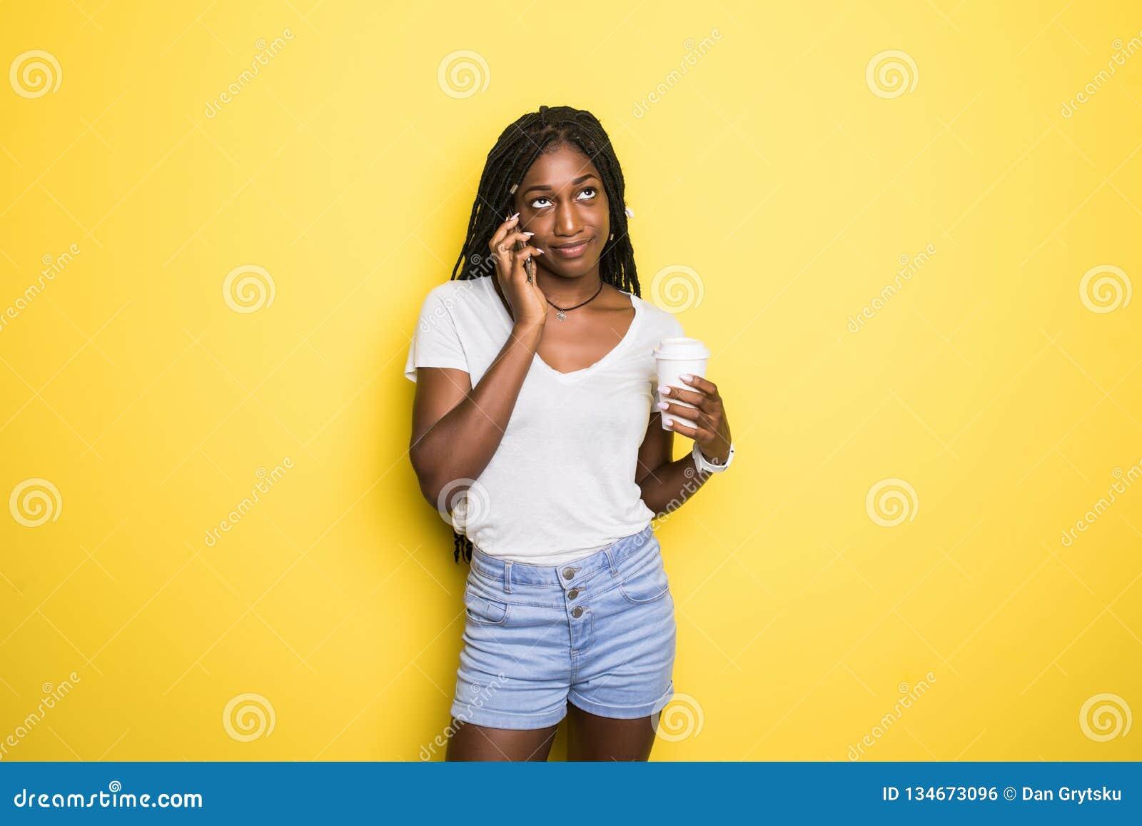 拿着纸杯用外带的咖啡的便衣的乐观非裔美国人的妇女,当谈话在被隔绝时的智能手机