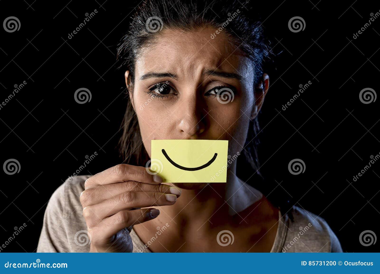 拿着纸的拉丁哀伤的沮丧的拉丁女孩掩藏她的在伪造品被画的微笑后的嘴