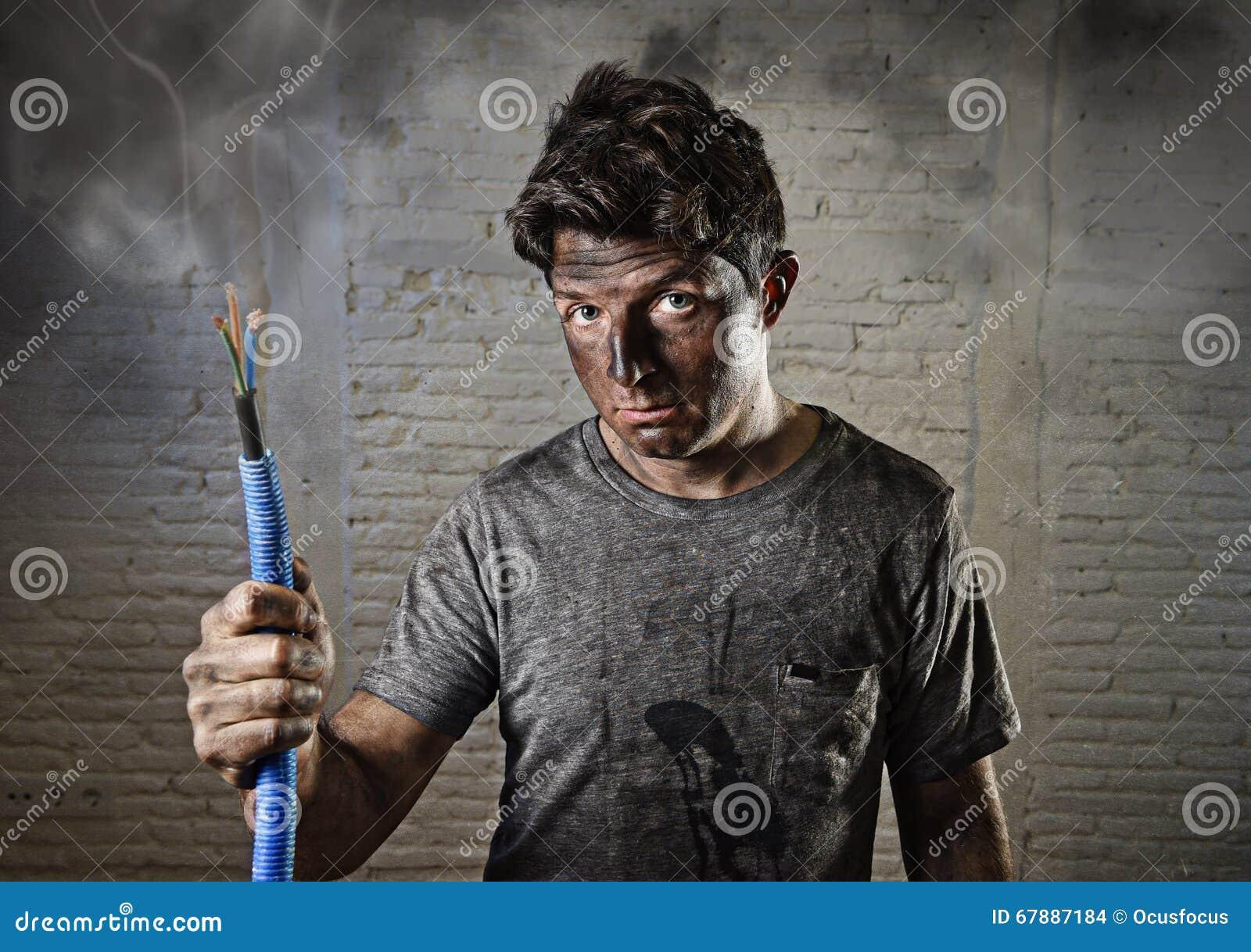 拿着缆绳的年轻人抽烟在与肮脏的被烧的面孔的电子事故以后在滑稽的哀伤的表示