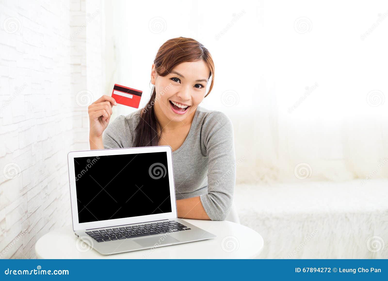 拿着网上购物的妇女信用卡