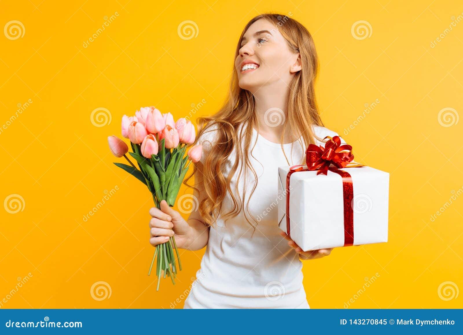 拿着美丽的花和一个礼物盒的花束愉快的女孩在黄色背景