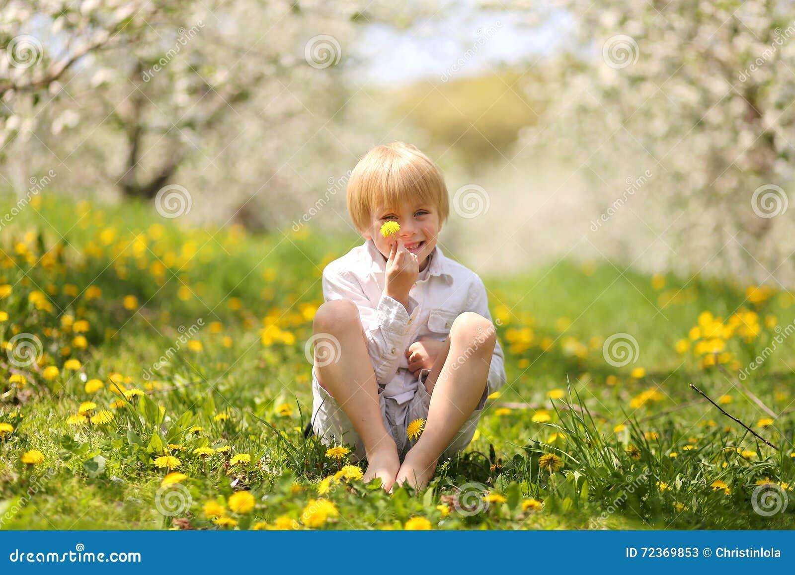 拿着花的甜小男孩在果树园