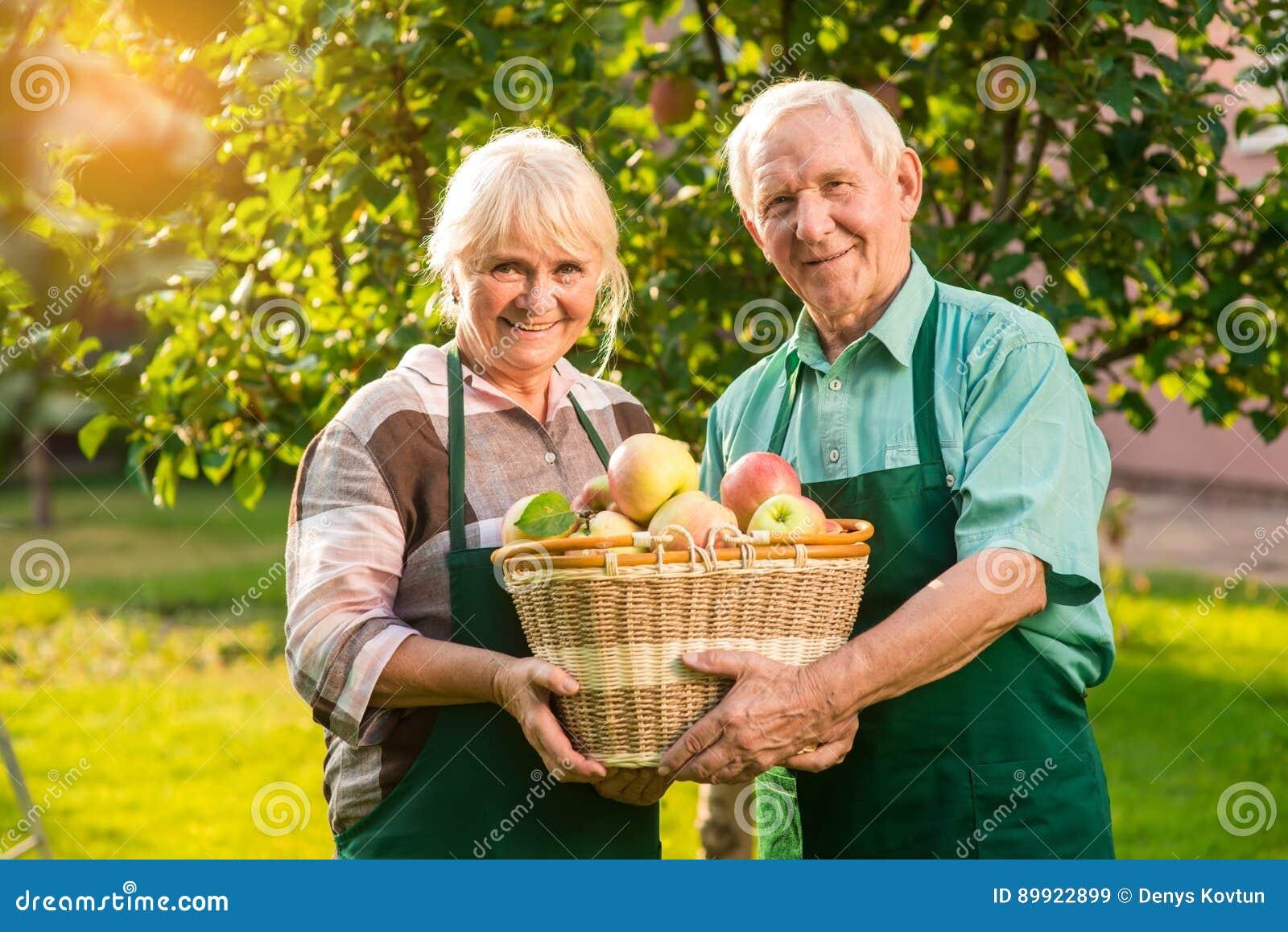 拿着苹果篮子的年长夫妇