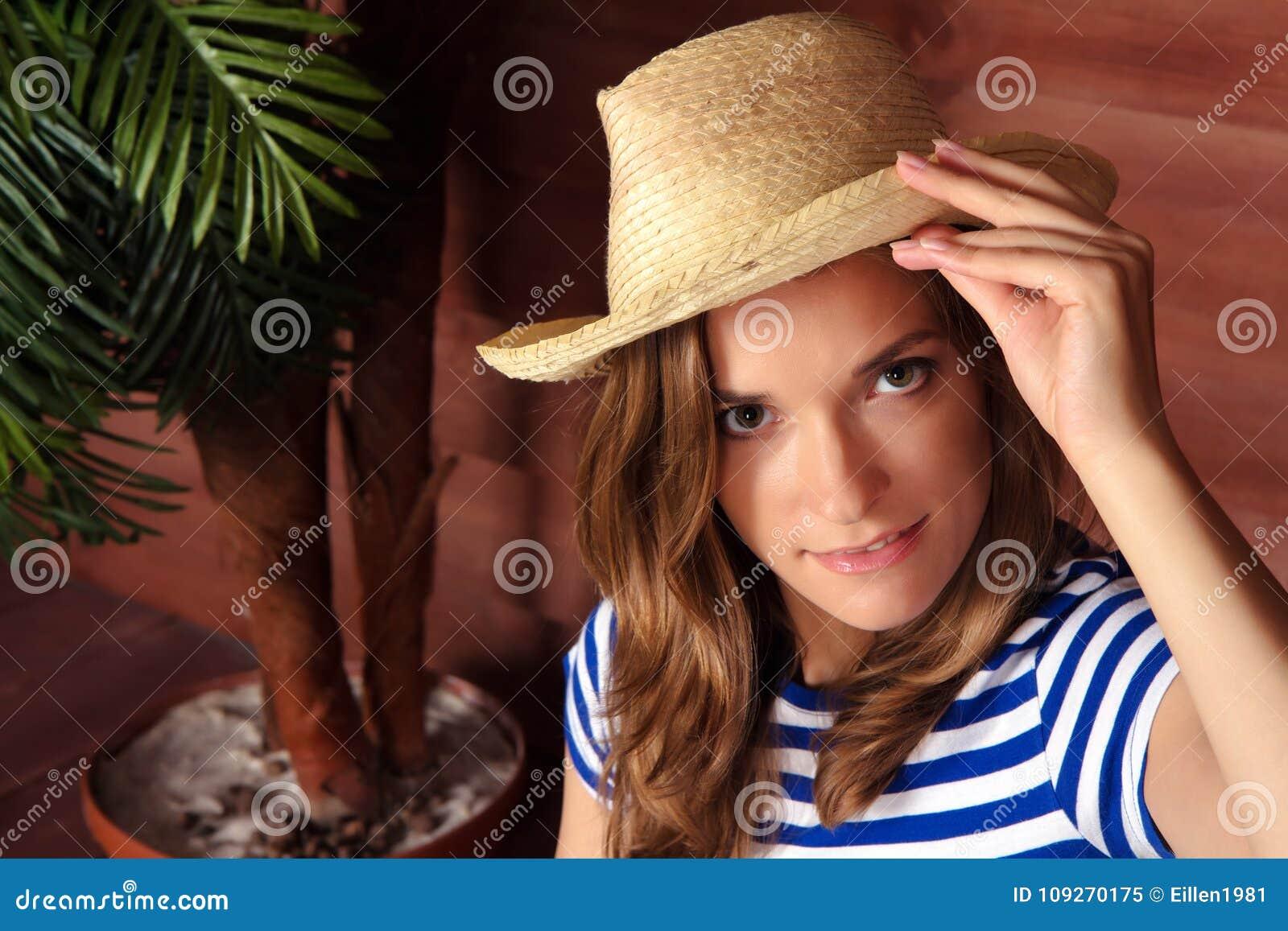 拿着草帽和坐在s的木房子附近的白肤金发的夫人