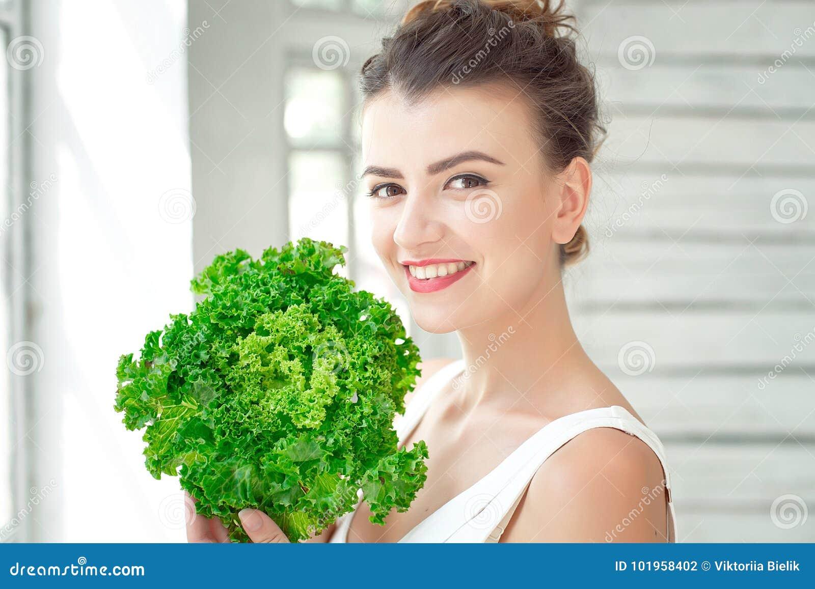 拿着莴苣的绿色叶子年轻逗人喜爱的女孩 Healtlife概念 室内射击
