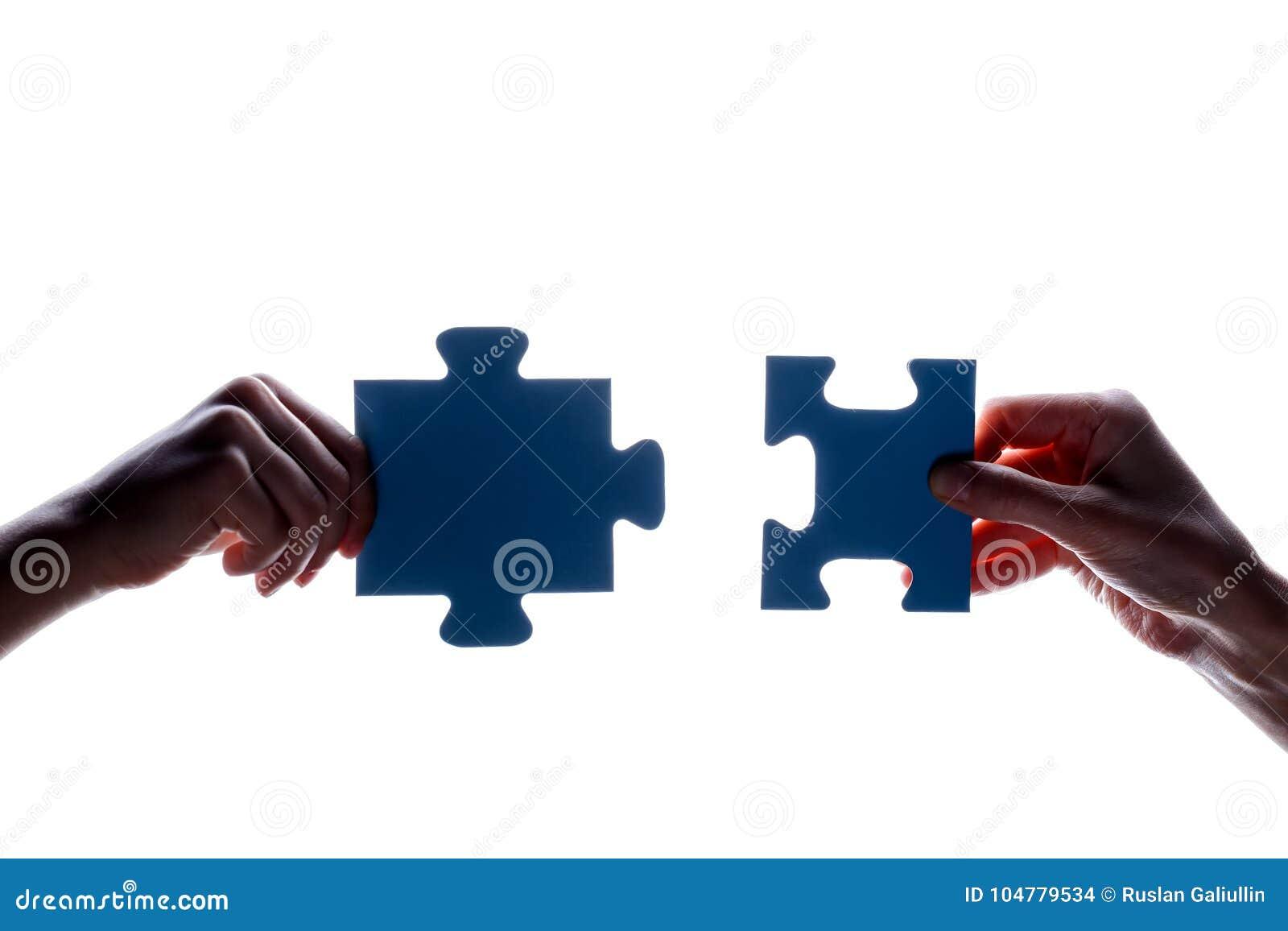 拿着蓝色七巧板片断的夫妇在白色背景的两手剪影  概念-连接想法,标志,标志, fr
