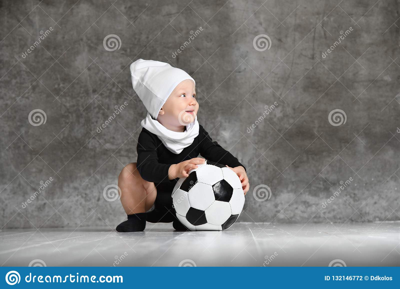 拿着足球的婴孩的逗人喜爱的图象