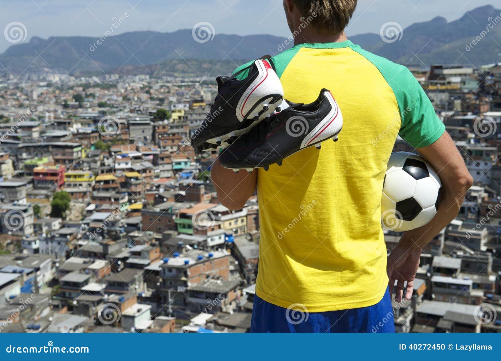 拿着足球Favela的成套工具的巴西足球运动员