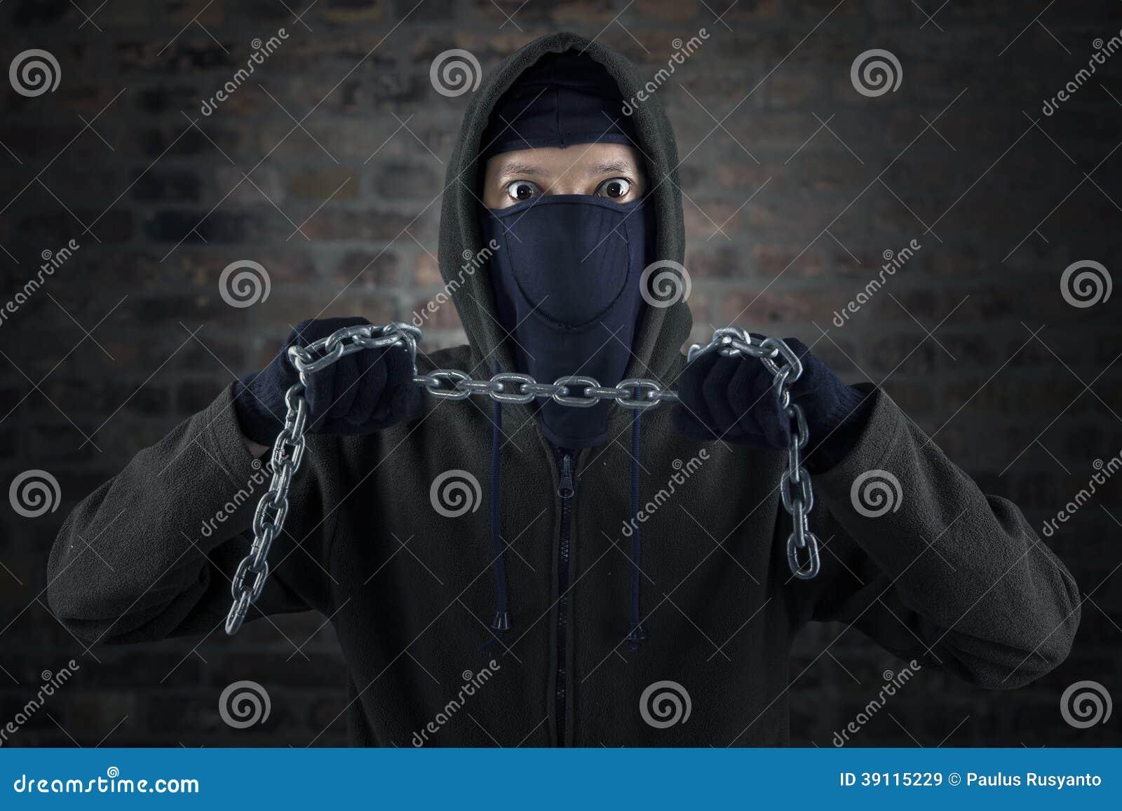 凶手_有站立在砖墙前面的链子的危险凶手.