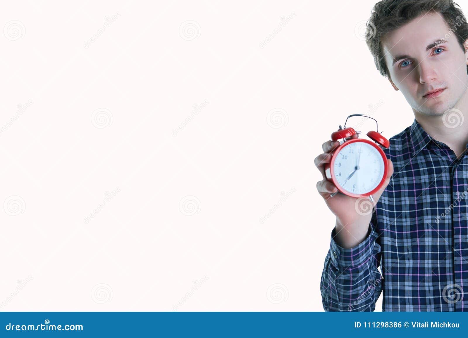 拿着闹钟的一个混乱的年轻人的特写镜头画象被隔绝在白色背景
