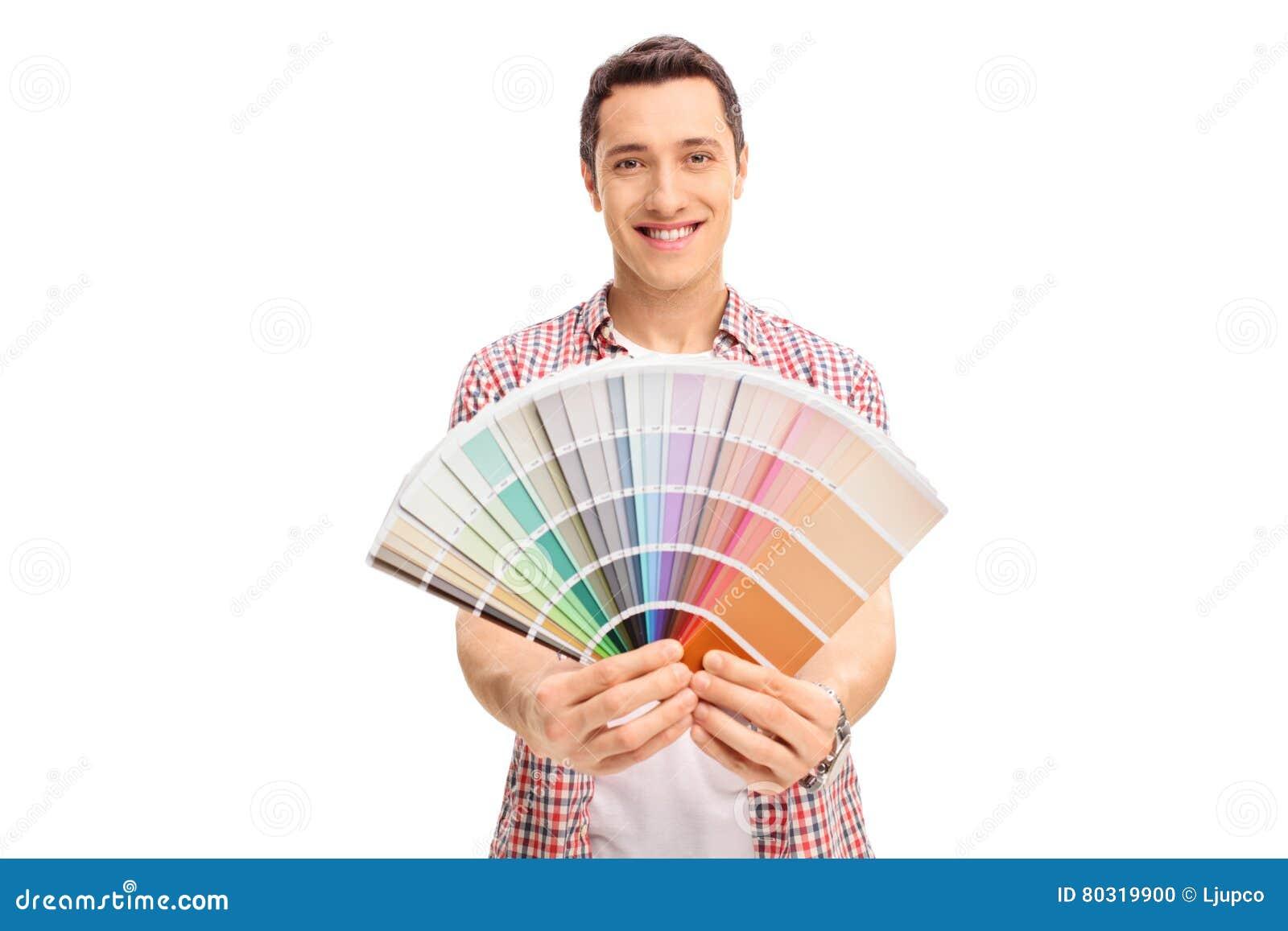 拿着颜色样片的愉快的年轻人