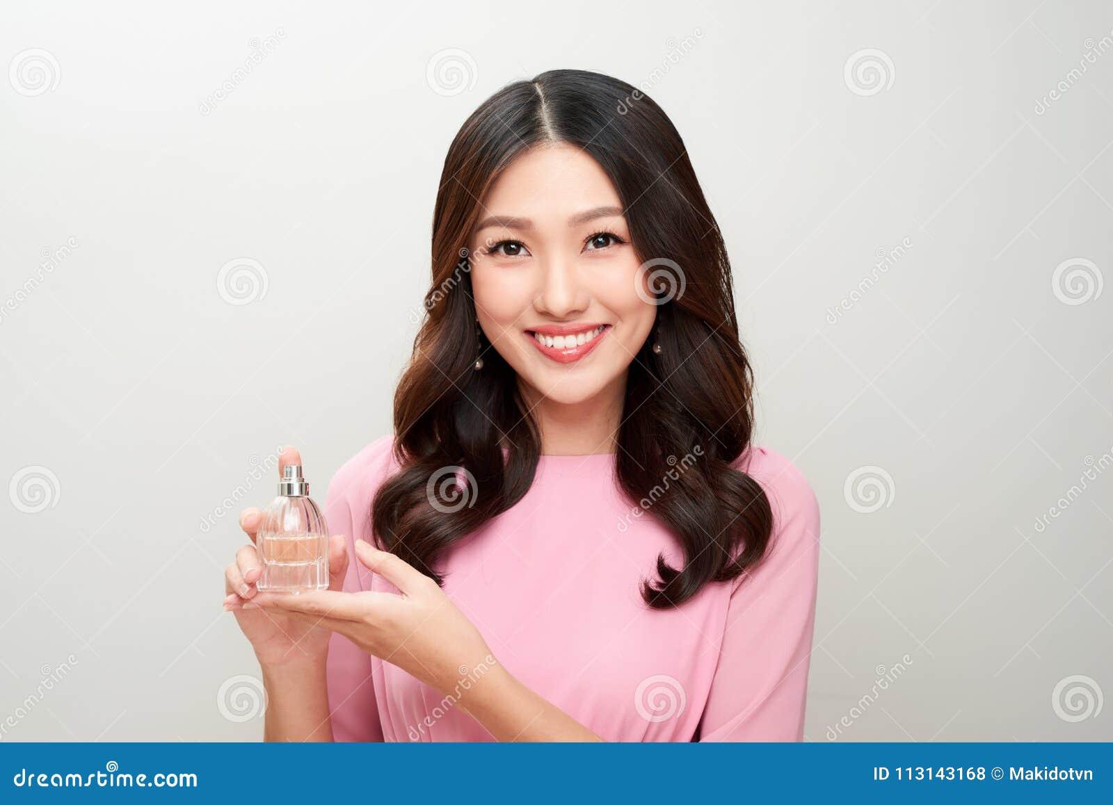 拿着香水瓶和应用它的美丽的亚裔妇女