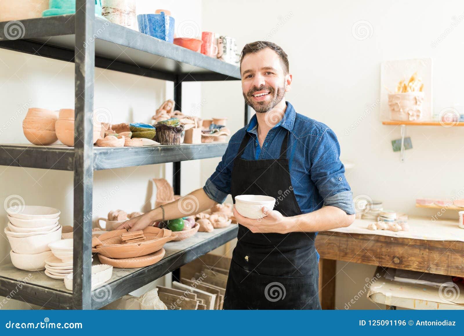 拿着黏土碗的工匠由架子在瓦器车间