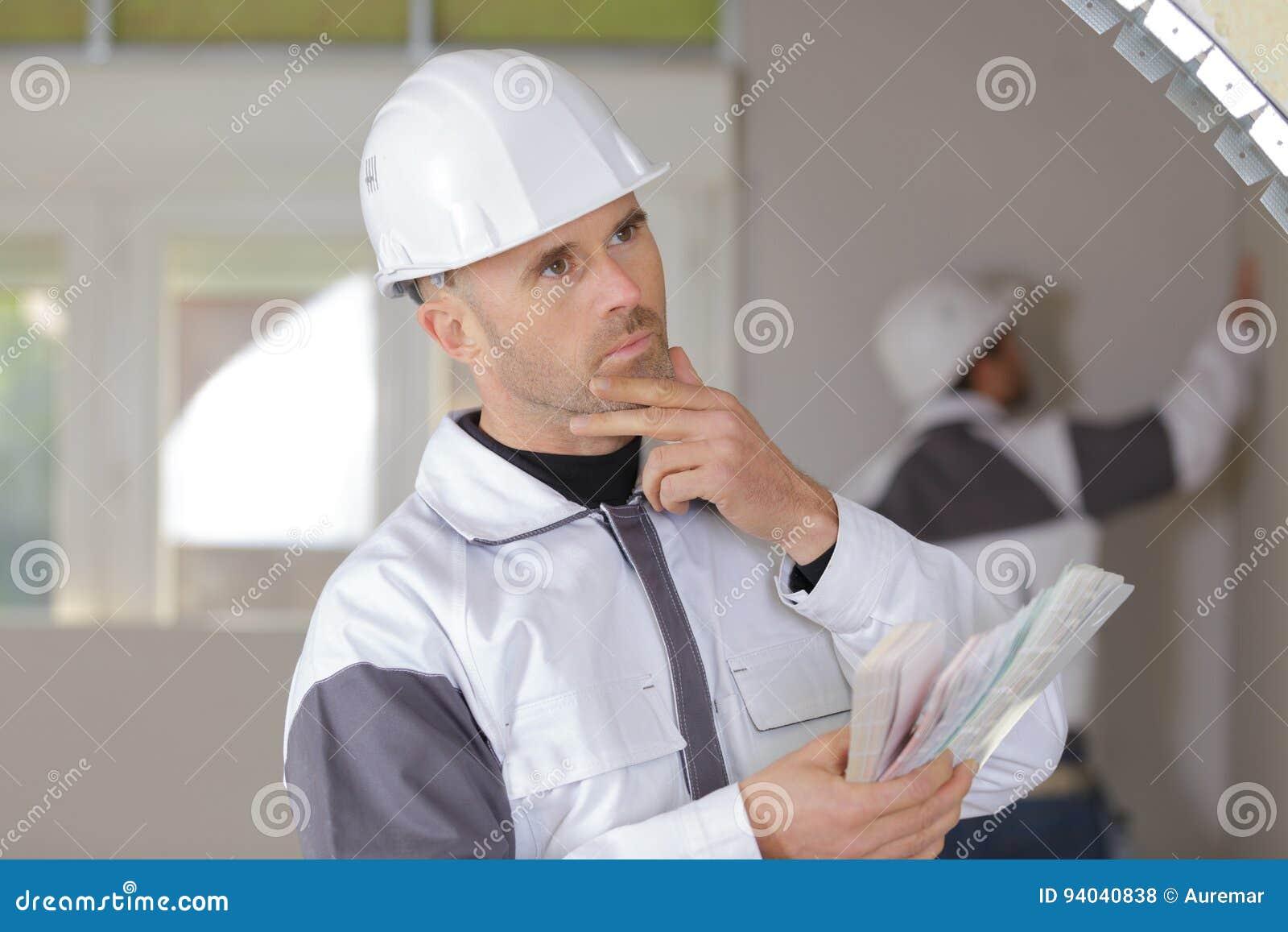 拿着水平仪的迷茫的建筑工人在新房里