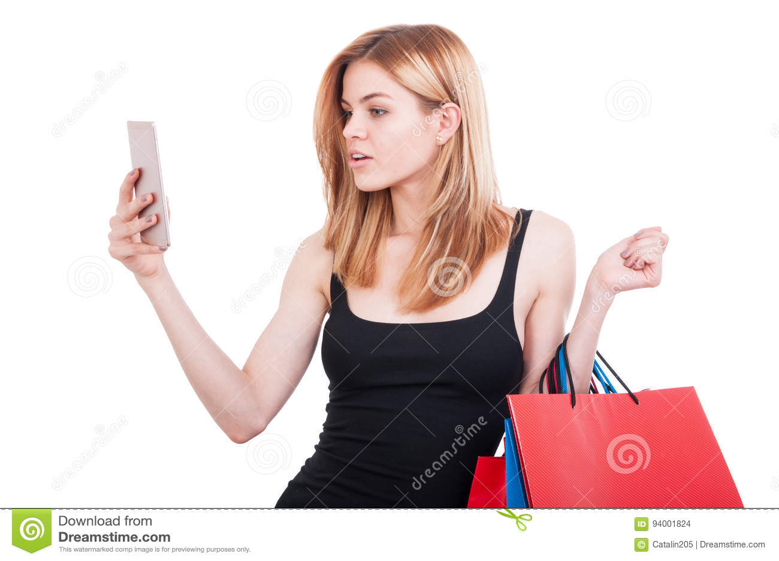 拿着购物袋的美丽的女孩浏览在智能手机