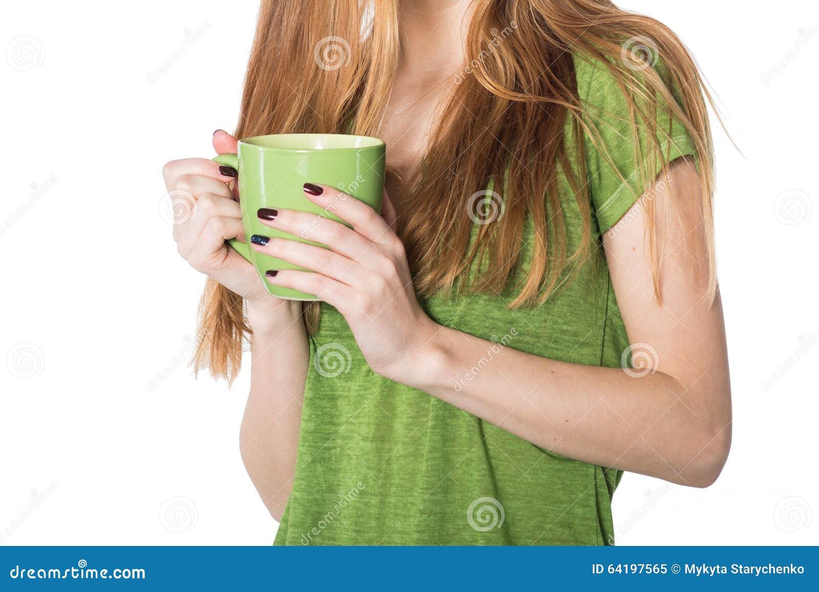 拿着绿色咖啡杯的美好的妇女手