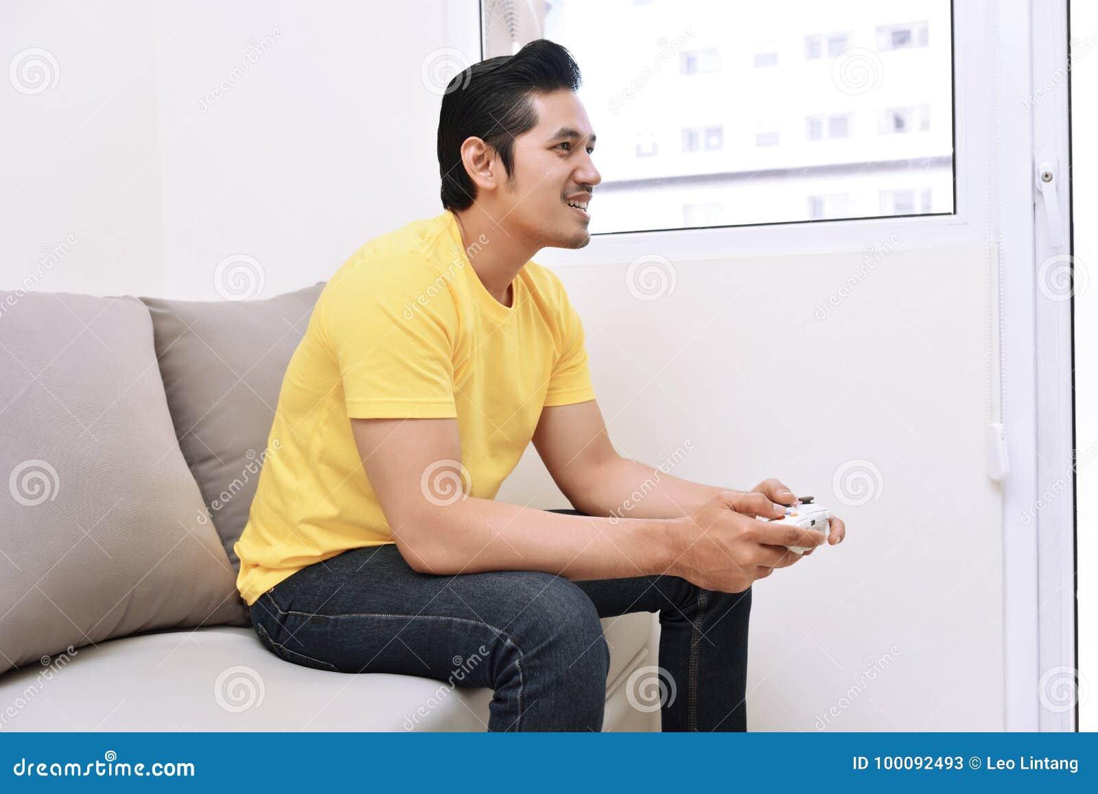拿着gamepad和打电子游戏的愉快的亚裔人