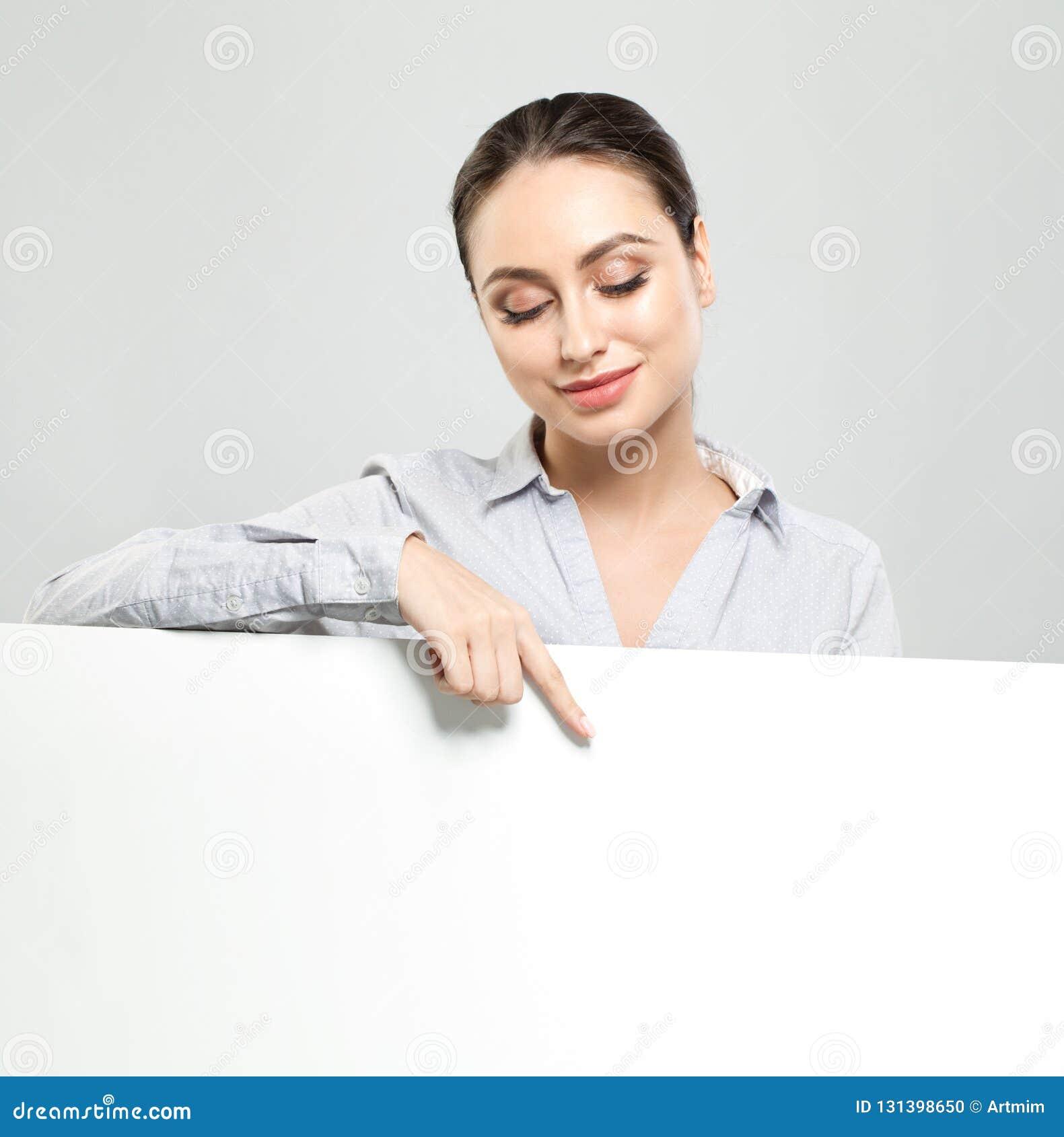 指向和拿着白色空的牌纸背景的友好的年轻女人 愉快的学生女孩、事务和教育